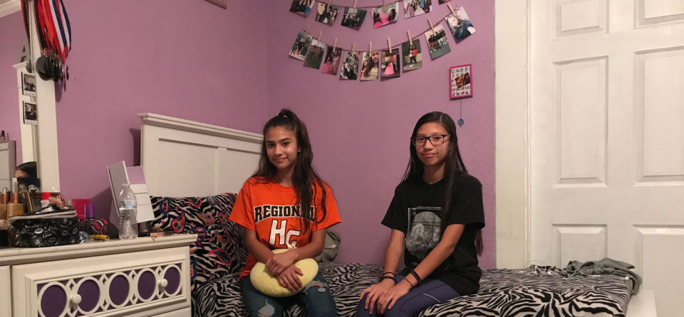 Abby Rubio, left, and her sister, Noemi, sit on Abby's bed in their shared bedroom.