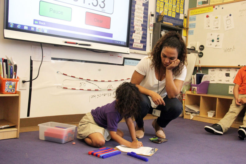 Mott Haven Academy Charter School teacher Carolina Garcia helps one of her fourth-grade students with an assignment. At Haven, all elementary school teachers have a co-teacher to allow them to give students more personalized attention.