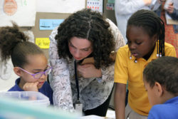 """Sasha Redlener, a fourth-grade teacher at Mott Haven Academy Charter School, helps her students with an assignment. Classes at the school mix """"body breaks"""" and other playtime with reading and math instruction and lessons in social and emotional skills."""