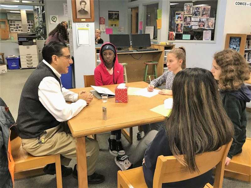 Seventh graders (clockwise from top) Emilia Faustino, Skylar Cook, Samantha Flynn and Rose Clews interview Luis Millones, a Colby College professor of Spanish, about his experiences as an immigrant from Peru.