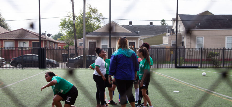 "Girls Coach Katie Lucky-Heard (left, white shirt) delivered a half-time pep talk to her team. ""Tú puedes,"" she said. You can do it."