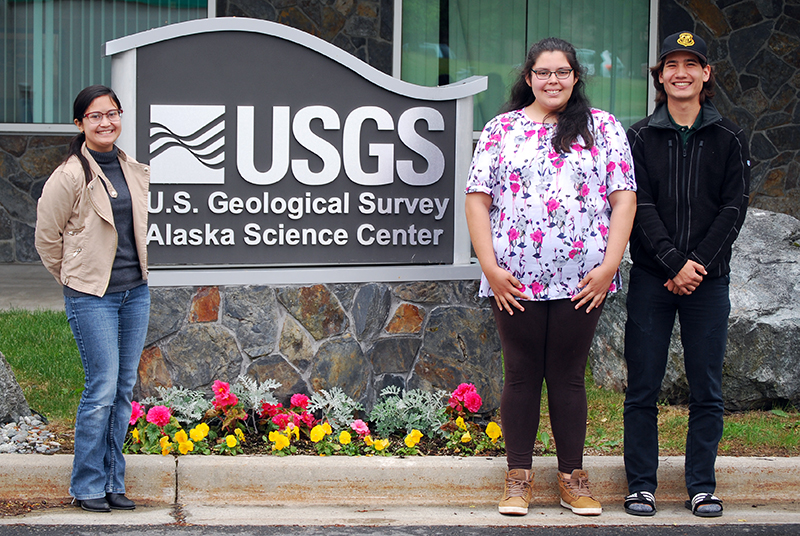 "Parker Pickett, 18, stands with Evangeline Dooc (left) and Lauryn Yates (center), both 18, his fellow U.S. Geological Service interns outside the agency's Anchorage office. In a departure from their parents' career paths, all three ANSEP students plan to pursue careers in the natural sciences. ""The opportunities I have been given are things [my parents] weren't able to have,"" Yates said."