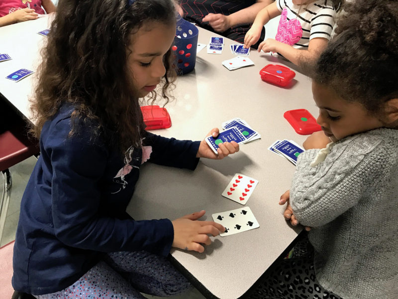 Leianny Menendez, 6, and Zariya Rodgers, 5, play a card game meant to help them improve their understanding of more and less towards the end of their full day of kindergarten at Dr. Norman W. Crisp Elementary School in Nashua, New Hampshire.