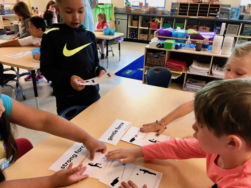 Kindergartner Lorenzo Glasser, 6, (Nike shirt) hands out illustrations to his Redmond, Oregon classmates for them to sort into according to whether a strong or gentle force is pictured.