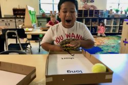 "Malachi Ballinger, 6, laughs at how far he has made his ""pinball"" travel during a science lesson in his kindergarten classroom in Redmond, Oregon."