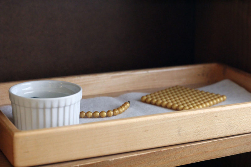 Montessori materials sit on a shelf in a primary classroom at Hill Country Montessori.