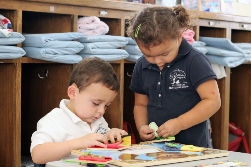 Two students work together in the primary classroom at Hill Country Montessori.