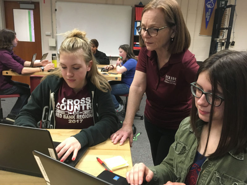 """In an effort to get more girls at Red Bank to participate in the cybersecurity challenge, teacher Mandy Galante, center, recruited girls from nontech classes, including a dozen from a creative writing class. """"We want to get the girls who never even thought of doing this,"""" she said."""