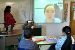 """Middle-schoolers in Colleen Johnson's social studies class participate in a Skype """"field trip"""" with a guest lecturer located in Virginia (shown on the screen). With greater bandwidth on a new fiber-optic internet connection, Nome teachers plan to do more live video streaming."""