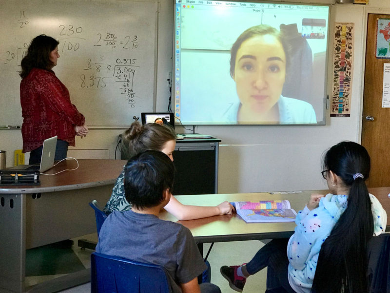 "Middle-schoolers in Colleen Johnson's social studies class participate in a Skype ""field trip"" with a guest lecturer located in Virginia (shown on the screen). With greater bandwidth on a new fiber-optic internet connection, Nome teachers plan to do more live video streaming."