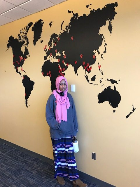 Sabariin Hidig, who was born in Kenya, stands in front of a mural at St. Paul College that shows students' countries of origin.
