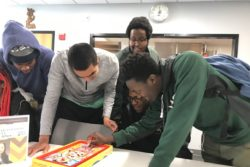 Adley Nyakora, a freshman at Minnesota State University, Mankato, plays Operation, while Cornelius Bright, Elijah Calderon-Pitchford, Aburrahman Guantai, and Jordan Headley look on.