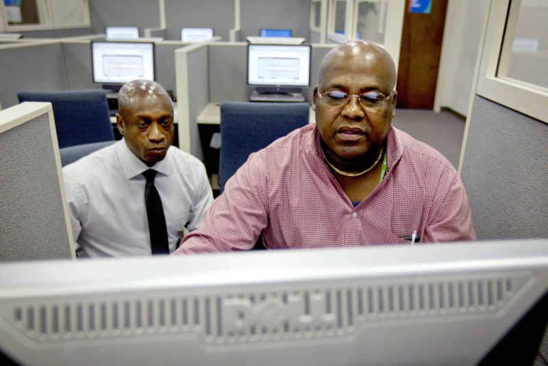 Army veteran Chester Dixon, right, works with William Moore, Georgia Department of Labor veterans representative, to apply for a new skills-based program to get out-of-work veterans trained and back in the job market, in Atlanta. The program is open to veterans between the ages of 35 and 60.