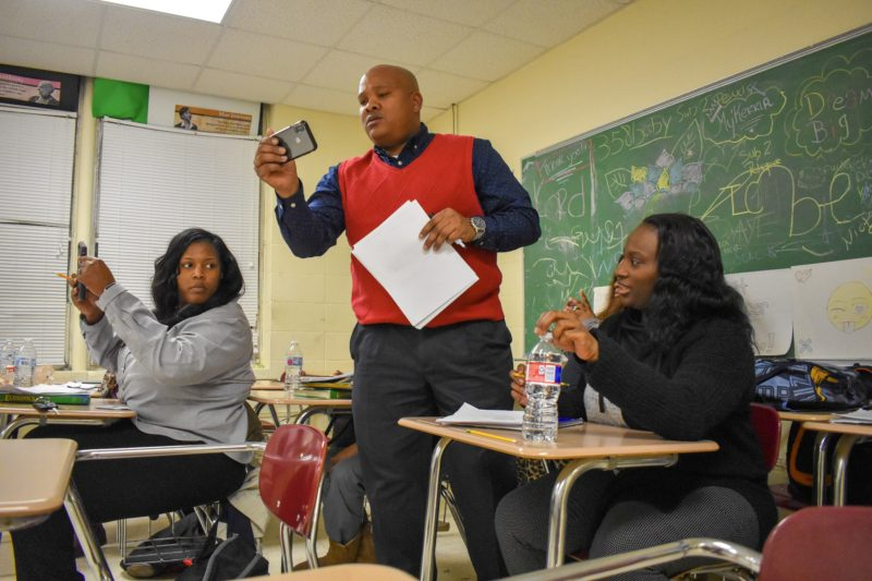 Aallyah Wright Solutions 2. Tony Young, center, former administrator in Coahoma County and current RISE instructor, helps students navigate math equations using their cell phone calculators during an evening RISE teacher certification cohort class at Coahoma Early College High School in late January.