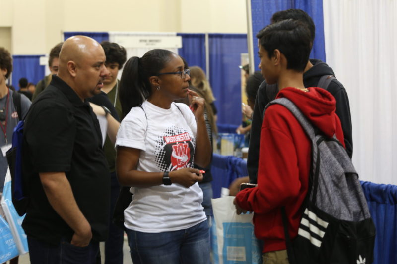 College counselor Oliver Rivas and his colleague, Veianca Millet, counsel students from Westchester Enriched Sciences Magnets high school at a college fair in Pasadena, California. Overcrowding on California's public campuses means that students with grade-point averages as high as 3.5 can't get in, Rivas says; now they're considering out-of-state schools that are only too happy to have them.