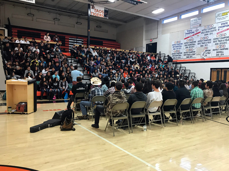 This year's adult retreat leader, history teacher Ned Dougherty, addresses the whole freshman class (sitting in bleachers) and the 80 seniors who participated in the annual three-day retreat at Taos High in October 2018.