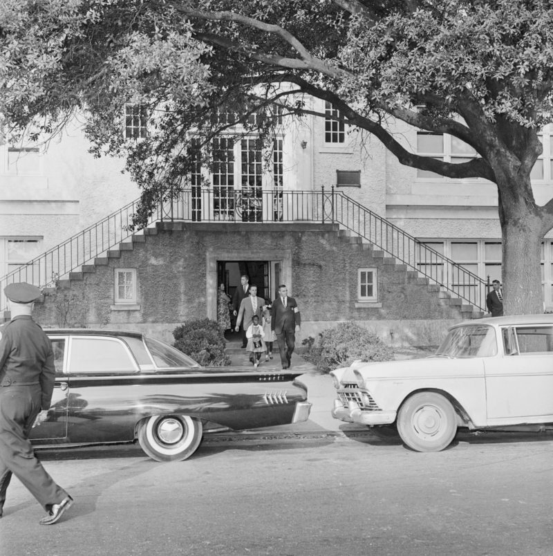 Three girls leave the previously all-white McDonogh 19 Elementary School after spending their second day in the newly desegregated school. The girls are delivered to the school in the morning and are called for in the afternoon by the U.S. marshals who are shown escorting the girls from the school.