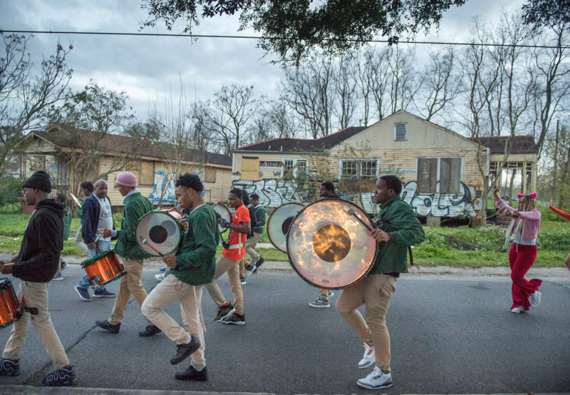 The band practices marching in an isolated section of the 9th Ward, where some houses are still shuttered from flood damage they suffered after Hurricane Katrina. George Washington Carver School band in New Orleans gets ready for Mardi Gras in February 2019.
