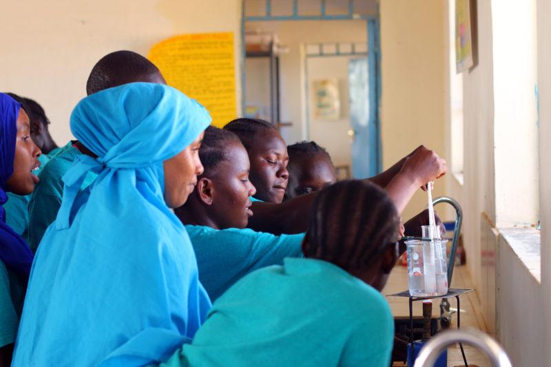 Los estudiantes de Morneau Shepell Secondary School for Girls se amontonan alrededor de un mechero Bunsen durante un laboratorio de química.  La escuela gasta $ 700 por alumno cada año, unos $ 550 más que otras escuelas secundarias en el campamento, pero aún no tiene suficientes libros de texto y materiales para repartir.