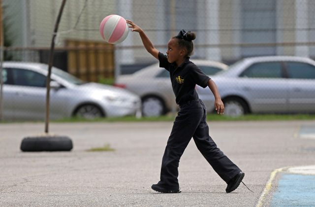 Second grader Jana Hicks plays in the schoolyard at ReNEW SciTech Academy, a charter school in New Orleans, Thursday, Aug. 14, 2014. (AP Photo/Gerald Herbert)