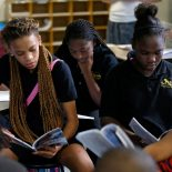 Sixth grade students Miracle Roberson, left, Darion James, and Brianetay Martin, right, read during literature intervention class at ReNEW SciTech Academy, a charter school in New Orleans, Thursday, Aug. 14, 2014. (AP Photo/Gerald Herbert)