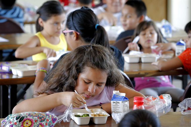Children eat a free lunch at the Phoenix Day @ Central Park Youth Program in downtown Phoenix, Tuesday, July 22, 2014. The grant-based lunch and dinner program provides free meals to children ages 5 to 18 in the immediate neighborhood surrounding the facility. (AP Photo/Matt York)