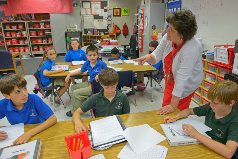 Belle Chasse Primary School 4th graders Zachary Davis, left, Bella Gross, Julianna Shipp, Nickolas Farrington, Cody Gaubert, Dante Compton, Emily Hotard, and Matthew LaRoche listen to Mary Beth Newchurch as they look over a reading passage from their writer's binders to determine if the passage was written in First, Second, or Third Person point of view in Belle Chasse, La. Thursday, April 3, 2014. (Photo: MATTHEW HINTON/Advocate)