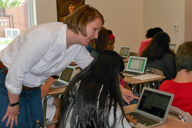 North Iredell Middle School English teacher Lori Meyer guides an eighth grade student in a class writing assignment on her laptop. (Photo: Margaret Ramirez)