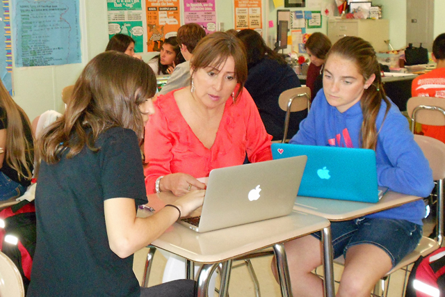 At Mt. Mourne International Baccalaureate Middle School, Spanish teacher Victoria Principe works with two students on their laptops during a blended learning rotation. (Photo: Margaret Ramirez)