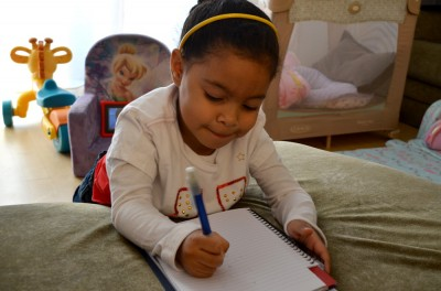 Allison, 4, practices writing her name on a notepad like she does in her pre-K class. (Photo by Jennifer Dev)