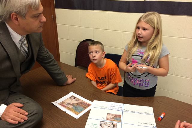 Fourth-graders Natalie and Dylan explains a project involving mapping and vocabulary to Principal Billy Bean. (Photo: Meredith Kolodner)