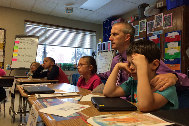 Reading teacher Eric Drumma helps third-graders Lila, Jeremiah and Kendra stay focused during a third-grade English lesson. (Photo: Meredith Kolodner)