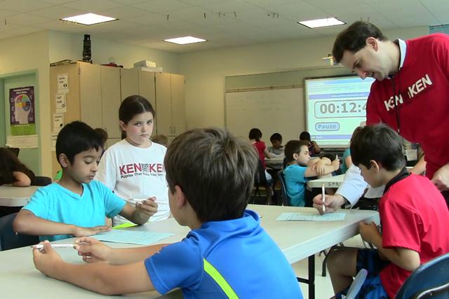 Springhurst's math specialist Josh Rosen reviews a third-grade finalist's work during the school's annual KenKen challenge. (Photo: Pat Wingert)