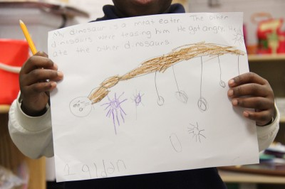 A pre-k student at Hazlehurst Middle School shows his completed work for the morning lesson about dinosaurs. Most of the students in the pre-k classroom are on track to meeting nationally recognized math and literacy goals, and are acclimated to the school environment. (Photo by Jackie Mader)