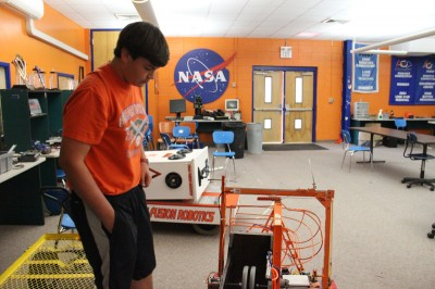 Jonathan Borho, a rising senior at Gulfport High School, examines a robot built by the high school robotics team for a recent competition. The school frequently teams with experts at NASA's Stennis Space Center to learn engineering and robotics. (Photo by Jackie Mader)