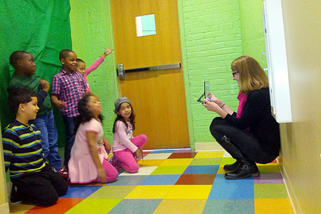 Carrie Sorensen, a teacher at Highlander Charter and a fellow with Fuse RI, works with students using a tablet computer. They are using an app to make a book cover. (Photo: Nichole Dobo)