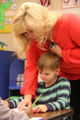 Charlotte McNeese helps a student with his writing assignment during a morning lesson. (Photo: Jackie Mader)