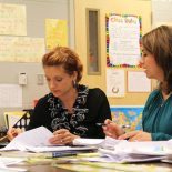 The principal of Madison Crossing, Martha D'Amico, explains how to grade student writing, while teacher Lela Hester looks on. (Photo: Jackie Mader)