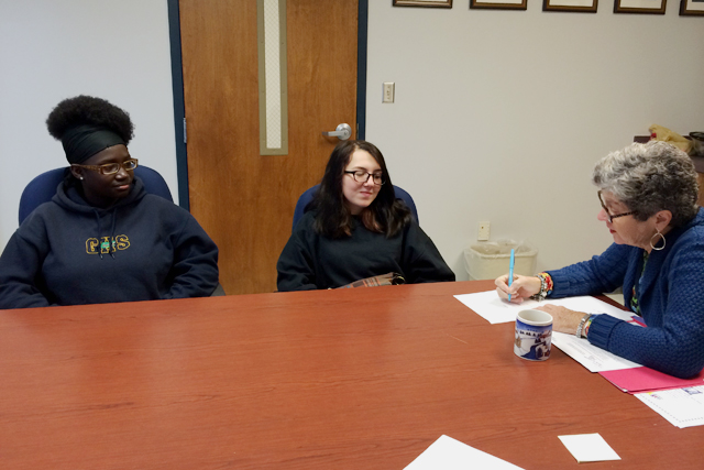 In Gautier, Miss., freshman Olandria Rayner (left) and junior Cecilia Cox go over their parent and student goals with Early Beginnings program director Connie Jo Williams. (Photo: Kayleigh Skinner)