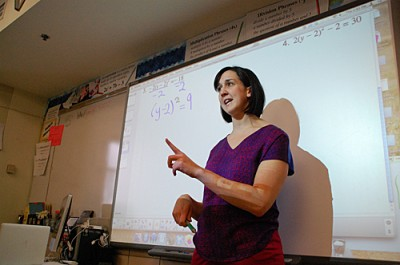 "Jessica Rice teaches ""support"" math to 9th graders at John F. Kennedy High School in Bloomington, Minn. It's the students' second math course of the day and acts as a supplement to their regular math class. Rice says the students need more time in math class to keep up with state standards. (Photo by Tim Post/MPR)"