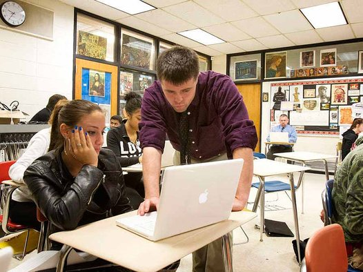 At Upper Darby High School, first-year teacher Joe Niagara works with senior Amanda Farina in class while Principal Christopher Dormer (seated, rear) observes and takes notes for Niagara's evaluation. (Photo courtesy Philadelphia Inquirer)