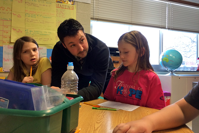 Third-grade teacher Tyler King leans in to explain math exercise to third-graders Trinity and Jaylene. (Photo: Meredith Kolodner)