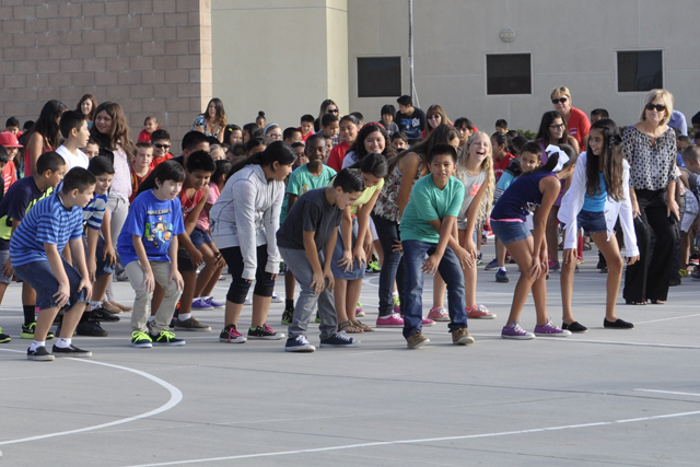 "Principal Debora Marks, far right, leads students at Corona-Norco Unified's Louis VanderMolen Fundamental Elementary in the ""cha cha slide"" on July 11 to energize the school for the day ahead. The year-round school of about 1,100 students began classes on July 7. The school has 55 percent high-needs students."