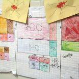 """Student work in the hallway of Eastside Elementary shows the """"partial product"""" method of solving a multiplication problem, one of many methods students have learned with Common Core. Many teachers say the new standards go deeper than the old standards and should not be dropped. (Photo: Jackie Mader)"""