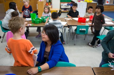 Teacher Pang Moua, who teaches all-day kindergarten, answers a question from a student while her class makes ABC books Wednesday, June 5, 2013 at Little Canada Elementary School. (Photo by Jennifer Simonson/MPR)