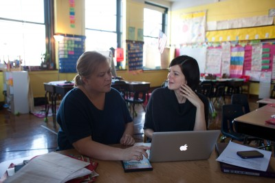 "Diane Meloscia (left), a third-grade teacher at Patrick Henry Ele-mentary School, meets with special education teacher Janet Ber-ka during their preparation period. ""As long as our students need us as much as they do, we will continue working the long hours regardless of the [time] the kids are in school,"" Meloscia says. (Armando L. Sanchez / Hechinger Report)"