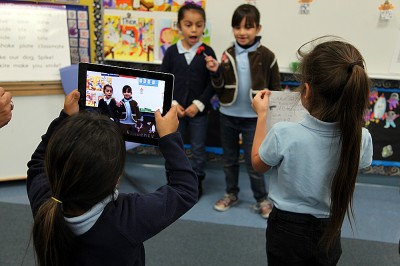 A student at Maywood Elementary takes video of her classmates as they interview each other about the careers they researched and wrote about as part of a class project.  (Photo: Brenda Iasevoli)