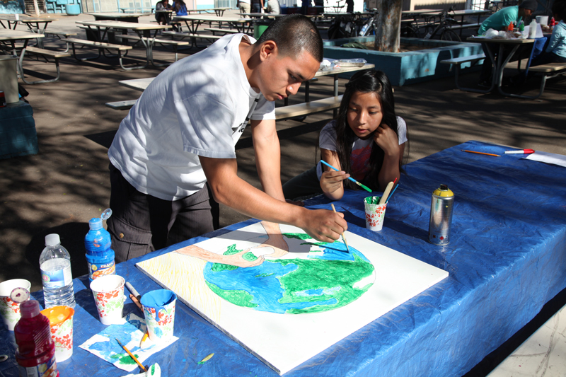 Pablo Dominguez, 21, paints a mural with his sister on volunteer day at Oscar Romero Charter School in central Los Angeles, where Dominguez's sister is in the sixth grade. (Photo: Brenda Iasevoli)
