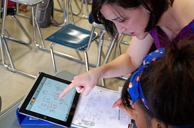 "Jessica Rice works with 9th grader Edinat Thoronka in a ""support"" math class.  ""We're doing our best to push them and catch them up, because they've been behind for whatever reason,"" Rice said. (Photo by Tim Post/MPR)"