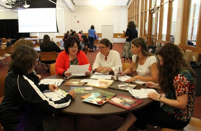 Teachers sort through a pile of non-fiction books during a June literacy training at Fort Lewis College. Students will be reading more non-fiction this year, especially in the high school grades. (Photo: Jackie Mader)